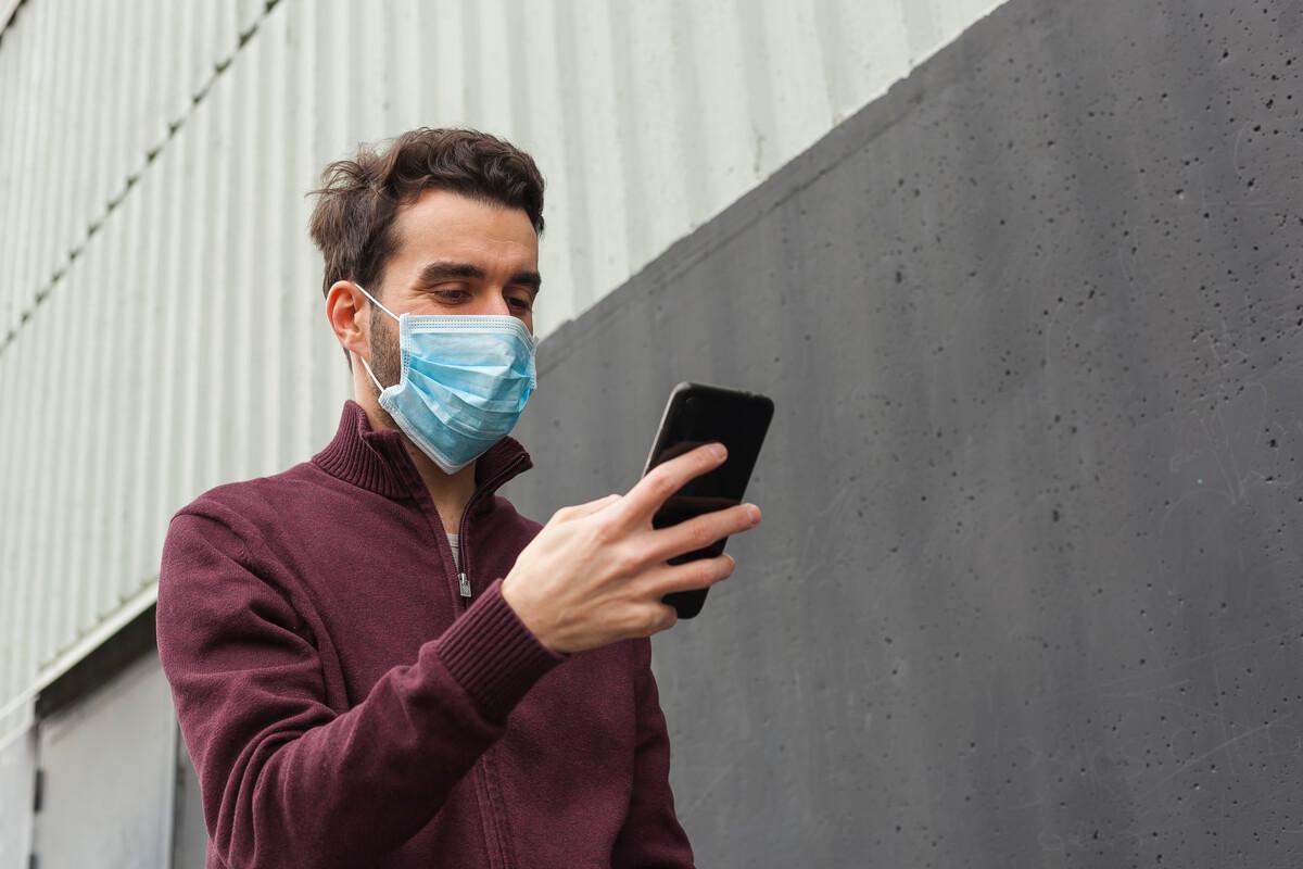 barbat cu masca protectie antivirus cu un telefon in mana